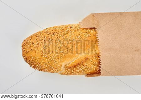 French Baguette In Craft Paper Bag. Long Loaf Of French Bread Isolated On White Background.