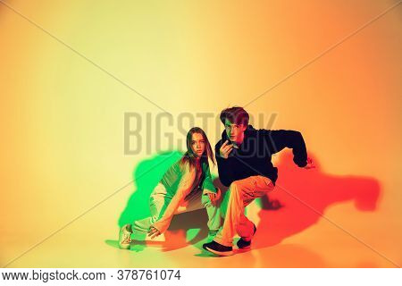 Young Man And Woman, Couple Dancing Hip-hop, Street Style Isolated On Studio Background In Colorful