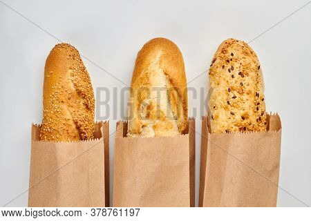 Three French Baguettes On White Background. Loaves Of French Bread In Paper Bags. Space For Text.