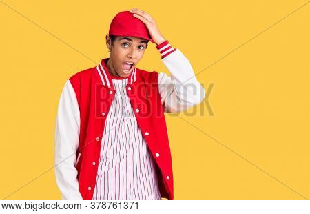 Young african amercian man wearing baseball uniform surprised with hand on head for mistake, remember error. forgot, bad memory concept.