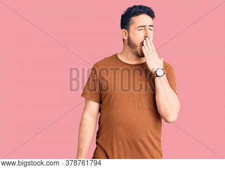 Young hispanic man wearing casual clothes bored yawning tired covering mouth with hand. restless and sleepiness.