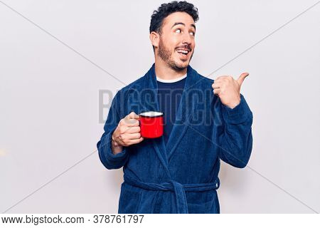 Young hispanic man wearing robe holding coffee pointing thumb up to the side smiling happy with open mouth