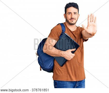 Young hispanic man wearing student backpack holding binder with open hand doing stop sign with serious and confident expression, defense gesture