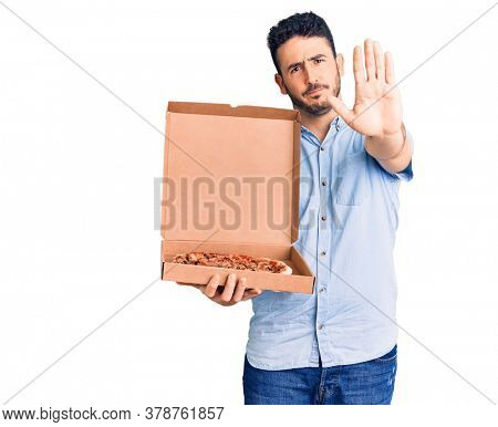 Young hispanic man holding delivery pizza box with open hand doing stop sign with serious and confident expression, defense gesture