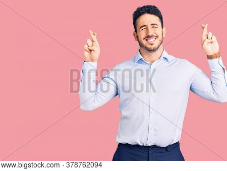 Young hispanic man wearing business clothes gesturing finger crossed smiling with hope and eyes closed. luck and superstitious concept.