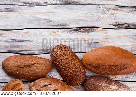 Wholemeal Wheat Bread Loaves And Copy Space. Homemade Bread Loaves On Vintage Wooden Background.