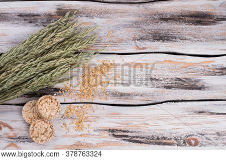 Oat Seeds, Ears And Puffed Crispbread. Round Crispbread And Oat Spikelets On Vintage Wooden Backgrou