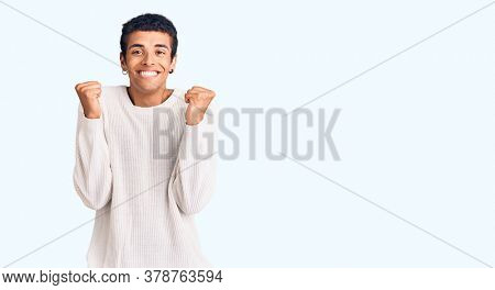 Young african amercian man wearing casual clothes excited for success with arms raised and eyes closed celebrating victory smiling. winner concept.