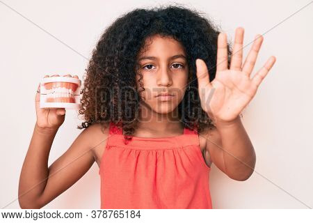 African american child with curly hair holding denture with open hand doing stop sign with serious and confident expression, defense gesture