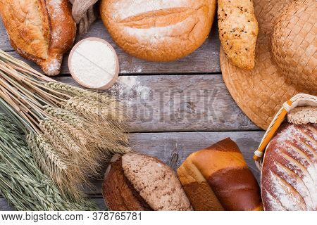 Organic Wheat Flour And Fresh Bread Assortment. Kitchen Still Life With Bread, Wheat Ears, Straw Hat