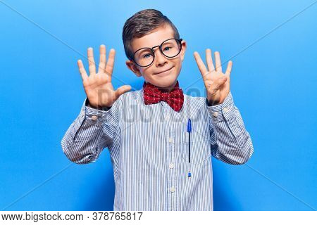 Cute blond kid wearing nerd bow tie and glasses showing and pointing up with fingers number nine while smiling confident and happy.