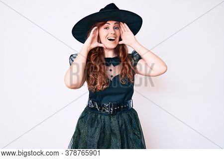 Young beautiful woman wearing witch halloween costume smiling cheerful playing peek a boo with hands showing face. surprised and exited