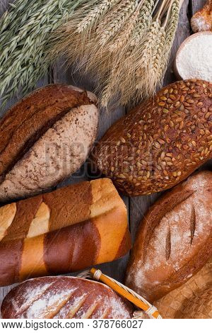 Bread On Wooden Background, Top View. Still Life With Artisan Bread And Wheat Ears. Healthy Food Con