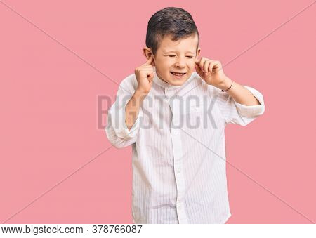 Cute blond kid wearing elegant shirt covering ears with fingers with annoyed expression for the noise of loud music. deaf concept.