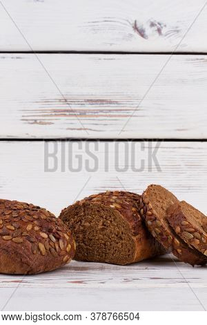Wholemeal Bread On Wooden Background. Loaf Of Rye Bread Cutting Into Slices. Space For Text.