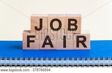 Job Fair - A Word Made Of Wooden Blocks With Black Letters, A Row Of Blocks Is Located On A Blue Not