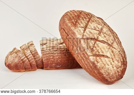 Two Loaves Of Dark Bread On White Background. Whole And Sliced Rye Bread Loaves. Healthy Bread Conce