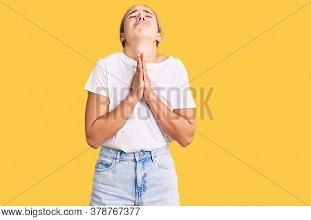 Young beautiful blonde woman wearing casual white tshirt begging and praying with hands together with hope expression on face very emotional and worried. begging.