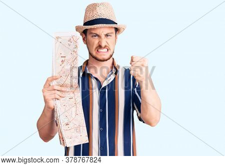 Young handsome caucasian man wearing summer hat holding city map annoyed and frustrated shouting with anger, yelling crazy with anger and hand raised