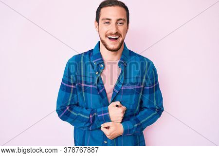 Young handsome man wearing casual clothes smiling and laughing hard out loud because funny crazy joke with hands on body.
