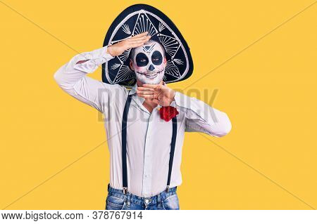 Man wearing day of the dead costume over background smiling cheerful playing peek a boo with hands showing face. surprised and exited