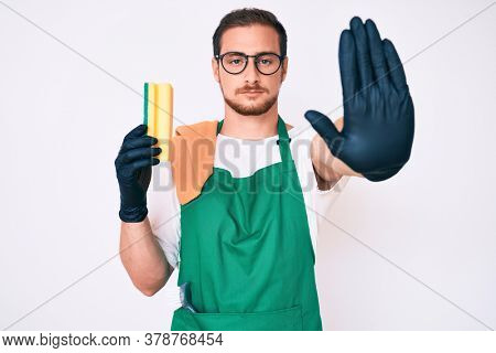Young handsome man wearing apron holding scourer with open hand doing stop sign with serious and confident expression, defense gesture