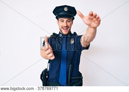 Young caucasian man wearing police uniform looking at the camera smiling with open arms for hug. cheerful expression embracing happiness.