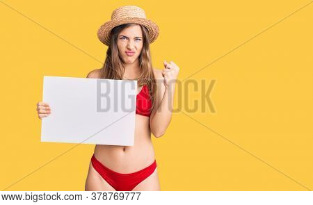 Beautiful caucasian young woman wearing bikini holding blank empty banner annoyed and frustrated shouting with anger, yelling crazy with anger and hand raised