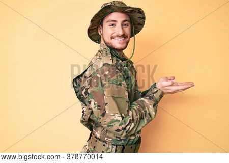 Young caucasian man wearing camouflage army uniform pointing aside with hands open palms showing copy space, presenting advertisement smiling excited happy