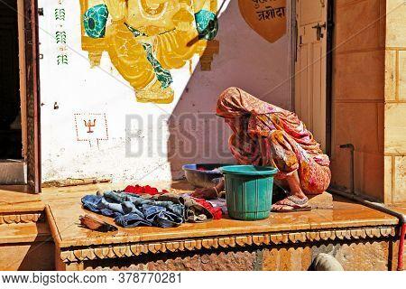 India day life. Jaisalmer old city' streets, woman washing clothes. Feb.2013 .Rajastan, India