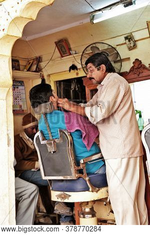 Indian people and their daily life living . Barber shop in Jaisalmer old tow in Rajastan. Feb.2013 India