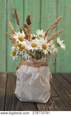 Bouquet Of White Chamomile Flowers With Dry Ears In A Kraft Paper Vase On A Shabby Wooden Turquoise