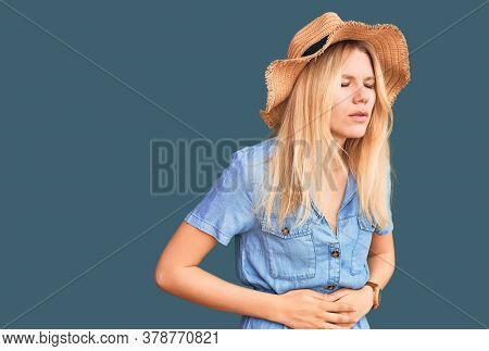 Young beautiful blonde woman wearing summer hat and dress with hand on stomach because indigestion, painful illness feeling unwell. ache concept.