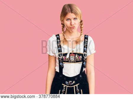Young beautiful blonde woman wearing oktoberfest dress depressed and worry for distress, crying angry and afraid. sad expression.