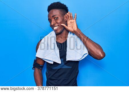 Young african american man wearing sportswear and towel smiling with hand over ear listening and hearing to rumor or gossip. deafness concept.