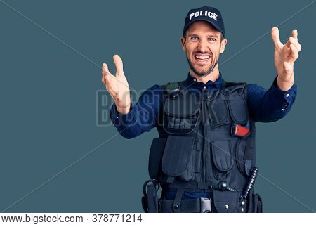 Young handsome man wearing police uniform looking at the camera smiling with open arms for hug. cheerful expression embracing happiness.