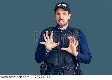 Young handsome man wearing police uniform disgusted expression, displeased and fearful doing disgust face because aversion reaction.