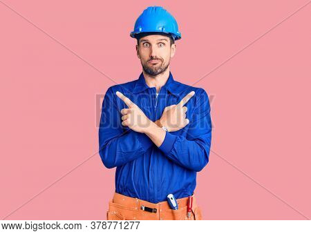 Young handsome man wearing worker uniform and hardhat doing thumbs up and down, disagreement and agreement expression. crazy conflict