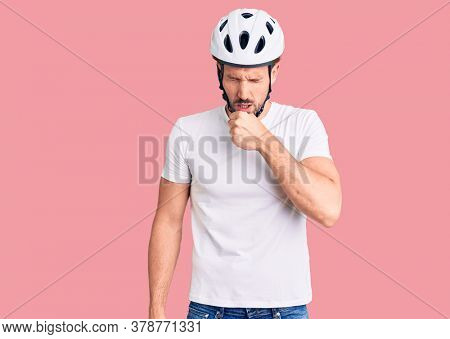 Young handsome man wearing bike helmet feeling unwell and coughing as symptom for cold or bronchitis. health care concept.