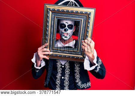 Young man wearing mexican day of the dead costume holding empty frame annoyed and frustrated shouting with anger, yelling crazy with anger and hand raised