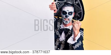 Young man wearing mexican day of the dead costume holding blank empty banner annoyed and frustrated shouting with anger, yelling crazy with anger and hand raised