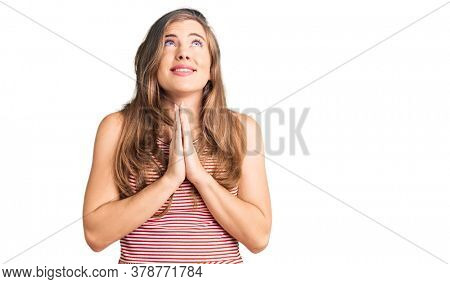Beautiful caucasian young woman wearing casual clothes begging and praying with hands together with hope expression on face very emotional and worried. begging.