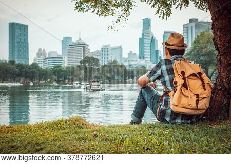 Young Man Tourists Sit And Watch The Cityscape Happily. At Public Park During The Travel On Holidays