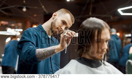 Young Hipster Guy Getting New Trendy Haircut In The Modern Barbershop. Professional Barber Cutting L