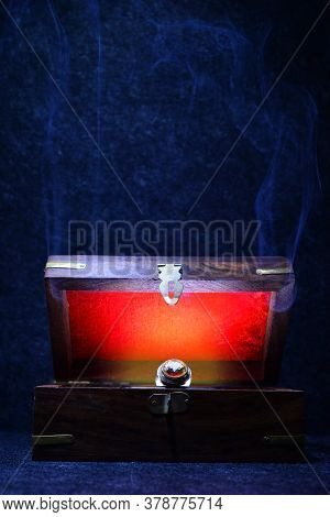 Antique Retro Wooden Box Ajar With A Jewellry Ring And A Red Light Inside It And A Smoke On A Dark B