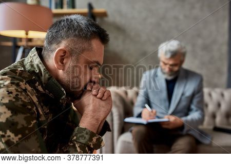 Middle Aged Military Man Closed Eyes During Therapy Session With Psychologist. Soldier Suffering Fro