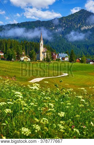 Austrian Alps. Beautiful mountain landscape with church Chapel and road in meadows with green grass. Traditional Alpine Village foggy morning scenic view with blue sky and clouds.