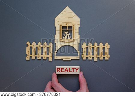 Model Of A Wooden House. Word 'realty' On Wooden Block. Male Hand, Wooden Fence. Copy Space. Busines