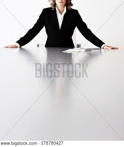 Cropped photo of businesswoman with hands on boardroom table