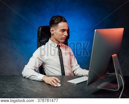 Busy Young Modern Men In Formalwear Working Using Computer. Studio Shot With Blue And Red Lights